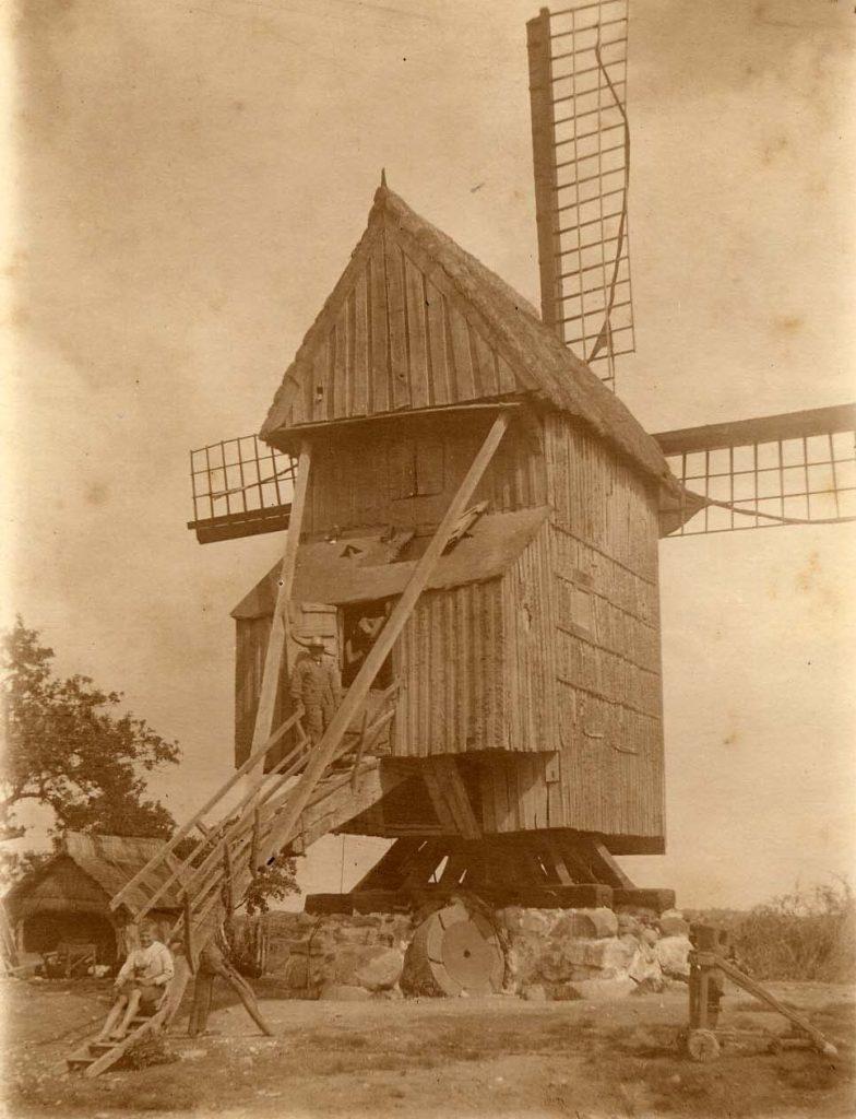 Stubmølle med mølleren på trappen. Krøjevognen der kan dreje møllen ses. Et træstativ på hjul.
